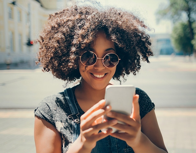 Girl with curly hair and round sunglasses holding mobile