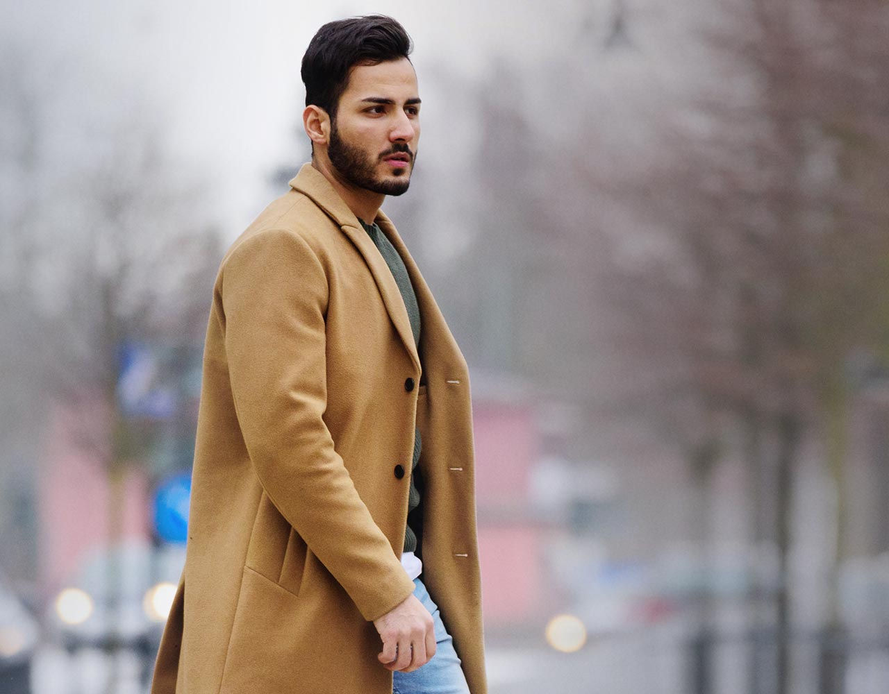 Man with a beard in a coat standing on a city street