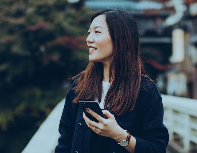 Asian woman in black coat with smartphone