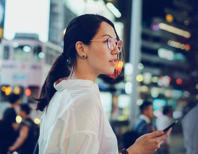 Asian lady with glasses holding smartphone