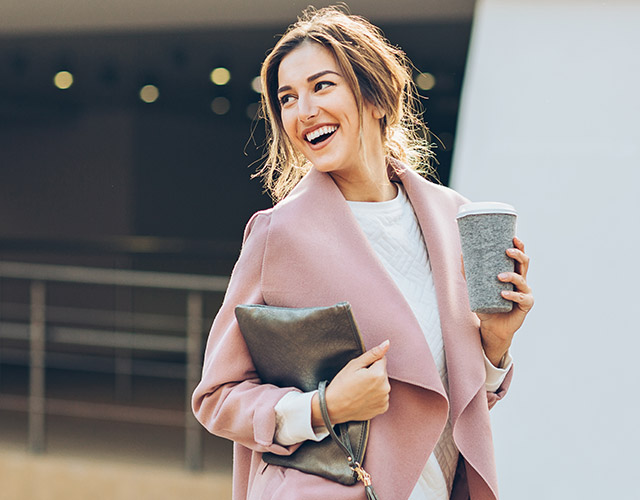 Smiling girl with clutch and coffee